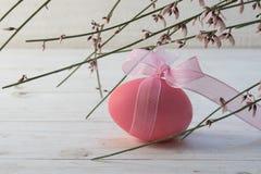 Ovos da páscoa cor-de-rosa com um ribon sob o genista ou a vassoura de florescência sobre Imagens de Stock
