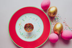 Ovos da páscoa cor-de-rosa e dourados coloridos com os confeitos que polvilham na placa Foto de Stock Royalty Free