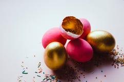 Ovos da páscoa cor-de-rosa e dourados coloridos com polvilhar dos confeitos Fotos de Stock