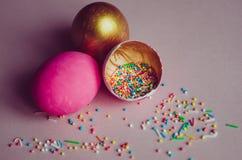 Ovos da páscoa cor-de-rosa e dourados coloridos com polvilhar dos confeitos Foto de Stock