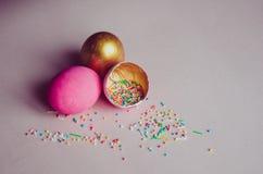 Ovos da páscoa cor-de-rosa e dourados coloridos com polvilhar dos confeitos Fotografia de Stock Royalty Free