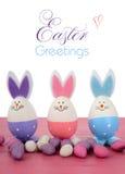 Ovos da páscoa cor-de-rosa, roxos e azuis do coelho Foto de Stock