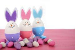 Ovos da páscoa cor-de-rosa, roxos e azuis do coelho Fotografia de Stock Royalty Free