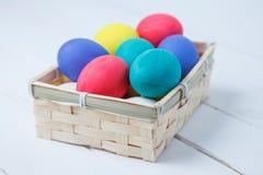 Ovos da páscoa da cor em de madeira na cesta do vintage Foto de Stock Royalty Free