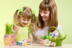 Ovos da páscoa da pintura da menina da matriz e da criança Foto de Stock