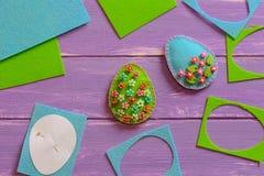 Ovos da páscoa de feltro do azul e do verde, sucata de feltro e folhas, molde de papel no fundo de madeira roxo Ofícios fáceis da imagem de stock royalty free