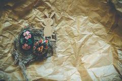 Ovos da páscoa de madeira coloridos e coelho de madeira das nádegas em um fundo do papel do ofício toned imagens de stock