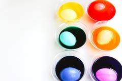 Ovos da páscoa de tingidura em uns copos plásticos Imagens de Stock