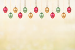 Ovos da páscoa de vidro decorativos que penduram em um fundo amarelo verde da mola Imagens de Stock Royalty Free