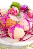 Ovos da páscoa com a fita cor-de-rosa na placa Imagens de Stock Royalty Free