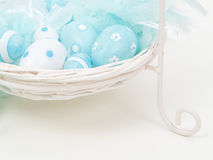 Ovos da páscoa decorativos azuis em uma cesta branca Imagem de Stock