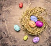 Ovos da páscoa decorativos coloridos, pintados no fim rústico de madeira da opinião superior do fundo do ninho acima Fotografia de Stock Royalty Free