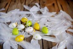 Ovos da páscoa decorativos com as penas brancas no fundo de madeira fotografia de stock