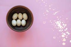 Ovos da páscoa decorativos em uma placa de madeira em um fundo cor-de-rosa imagens de stock