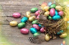 Ovos da páscoa do chocolate no estilo retro do ninho com escapes claros Fotografia de Stock