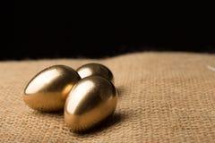 Ovos da páscoa do ouro em um fundo preto fotos de stock royalty free