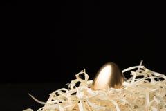 Ovos da páscoa do ouro em um fundo preto fotos de stock