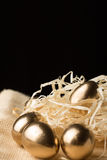 Ovos da páscoa do ouro em um fundo preto imagem de stock royalty free