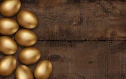 Ovos da páscoa do ouro no fundo de madeira escuro Fundo escuro r?stico r invitation imagem de stock royalty free