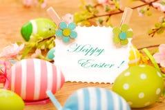 Cartão dos ovos da páscoa e de cumprimentos no fundo de madeira Fotos de Stock Royalty Free