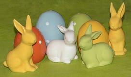 Ovos da páscoa e coelhinhos da Páscoa coloridos na frente de um fundo verde Fotos de Stock
