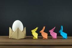Ovos da páscoa e coelhinhos da Páscoa coloridos, origâmi, acessórios para cartões e felicitações com Páscoa Imagens de Stock