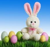 Ovos da páscoa e coelho coloridos na grama com céu azul Fotos de Stock Royalty Free