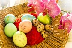 Ovos da Páscoa e de codorniz em uma cesta de vime com Foto de Stock Royalty Free