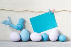 Ovos da páscoa e pássaro nas cores pastel com um cartão vazio em um fundo de madeira branco Foto de Stock Royalty Free