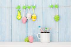 Ovos da páscoa e pincéis coloridos Foto de Stock