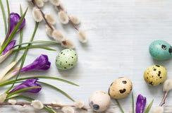 Ovos da páscoa e sumário floral no fundo de madeira Fotos de Stock