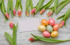Ovos da páscoa e tulipas com um cartão branco no fundo de madeira do vintage imagem de stock royalty free