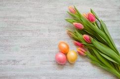 Ovos da páscoa e tulipas com um cartão branco no fundo de madeira do vintage imagens de stock royalty free