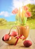 Ovos da páscoa e tulipas na tabela de madeira no fundo da mola Imagens de Stock Royalty Free
