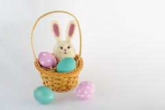 4 ovos da páscoa e um coelho na cesta pequena no fundo branco Imagem de Stock Royalty Free