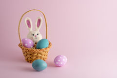 4 ovos da páscoa e um coelho na cesta pequena no fundo cor-de-rosa Foto de Stock