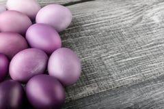Ovos da páscoa em cores elegantes em um fundo de madeira cinzento Fotos de Stock