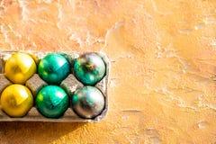 Ovos da páscoa em um papel dos painéis na tabela amarela Pintura do ovo da páscoa com o colorido durante a Páscoa bloco do canto  Fotos de Stock Royalty Free