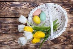 Ovos da páscoa em uma cesta branca com tulipas Imagem de Stock