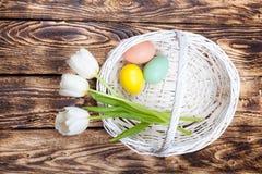 Ovos da páscoa em uma cesta branca com tulipas brancas Fotos de Stock Royalty Free