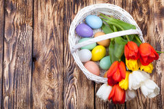 Ovos da páscoa em uma cesta branca com tulipas coloridas Foto de Stock