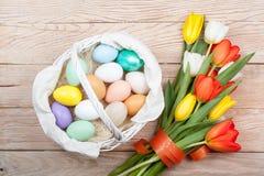 Ovos da páscoa em uma cesta branca com tulipas coloridas Imagens de Stock Royalty Free