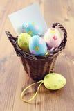 Ovos da páscoa em uma cesta com espaço da cópia em papel da observação Imagens de Stock Royalty Free