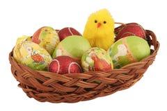 Ovos da páscoa em uma cesta com pintainho do brinquedo Fotos de Stock