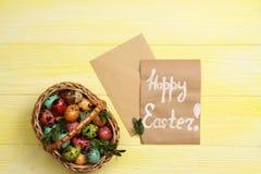Ovos da páscoa em uma cesta com um cartão feliz da Páscoa Fotografia de Stock