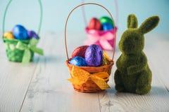 Ovos da páscoa em uma cesta com um coelho Fotografia de Stock