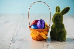 Ovos da páscoa em uma cesta com um coelho Fotos de Stock