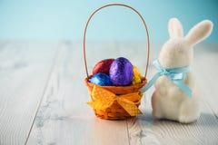 Ovos da páscoa em uma cesta com um coelho Fotografia de Stock Royalty Free