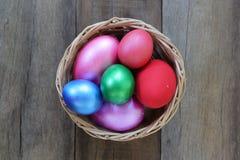 Ovos da páscoa em uma cesta de vime no fundo de madeira Imagens de Stock