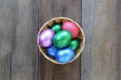 Ovos da páscoa em uma cesta de vime no fundo de madeira Imagem de Stock